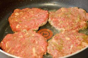 moose meat burgers cooking in a pan