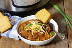 instant pot chili served in a white bowl and topped with shredded cheese and green onions