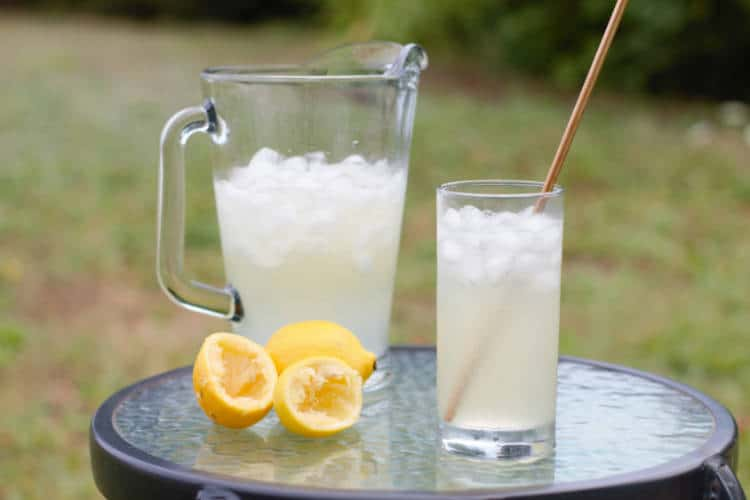 old fashioned lemonade served in a glass with a metal straw on a table outside