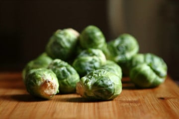 individual raw brussel sprouts on a wood surface