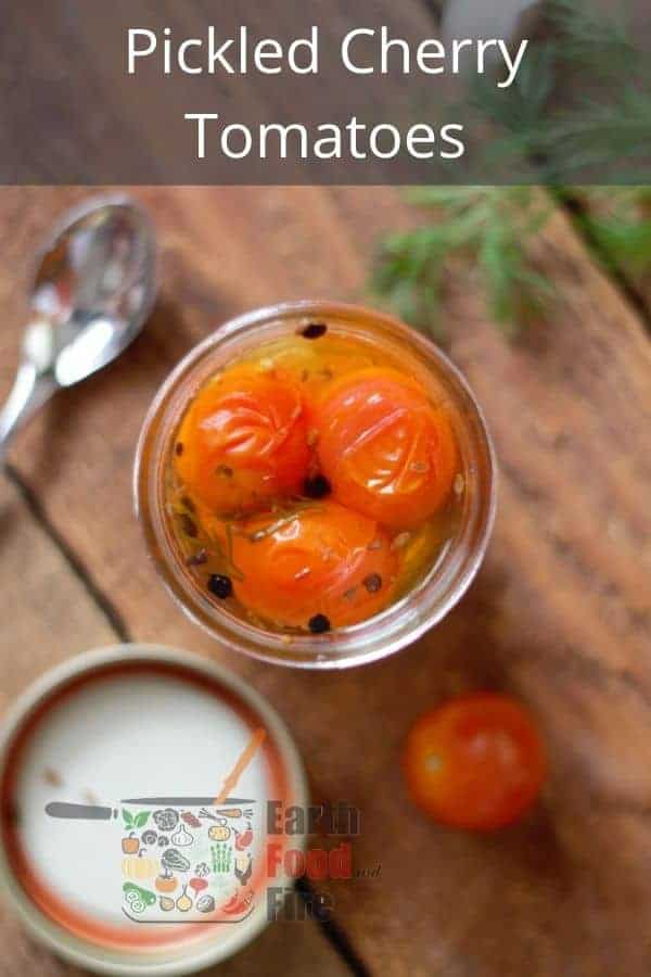 overhead shot of pickled cherry tomatoes in a mason jar with pinterest text overlaid