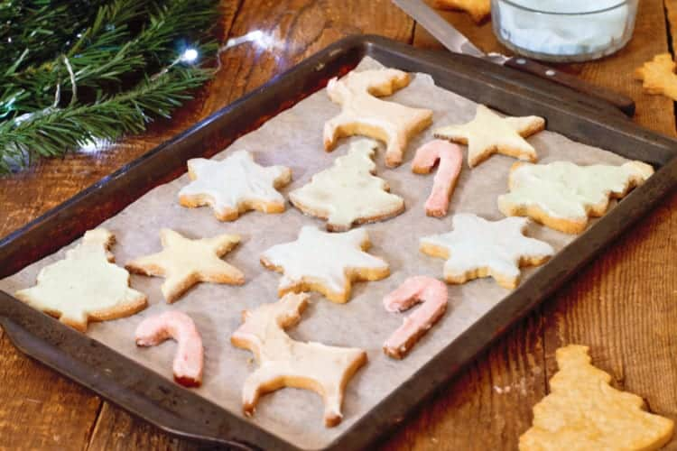 simple festive sugar cookies on a baking tray on a rustic wooden counter.