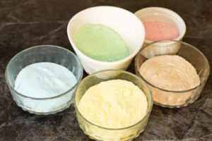 small dishes with pastel colored sugar in each