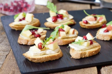 warm brie crostini's topped with a fresh apple and pomegranate salad on a black slate serving board