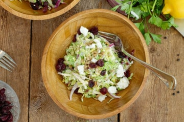 Overhead shot of shaved brussels sprout salad in a rustic wooden bowl, garnished with dried cranberries and goat cheese