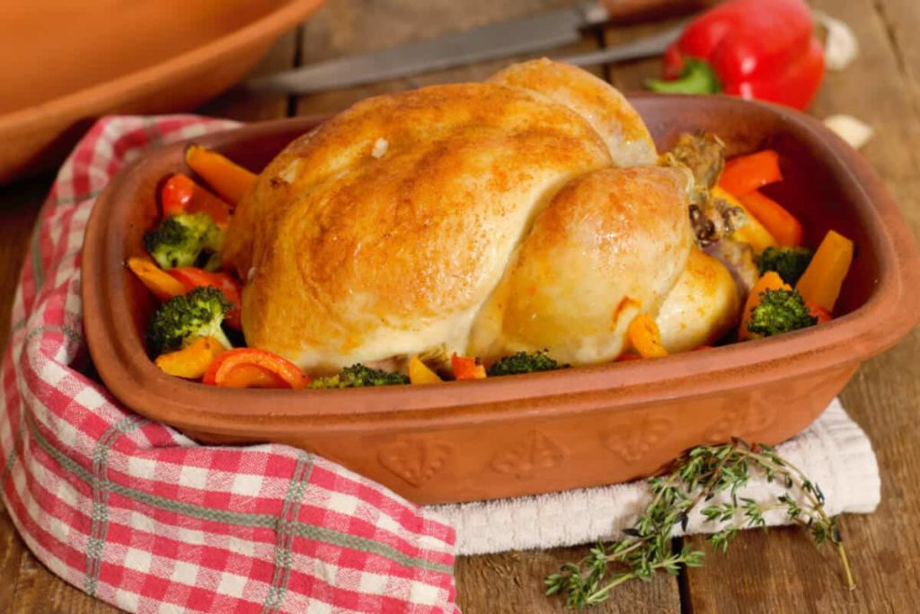 whole roasted chicken in a clay baker surrounded by bell peppers and broccoli