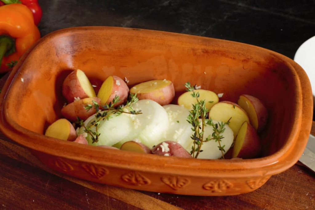 placing potatoes and onions in the clay baker with herbs