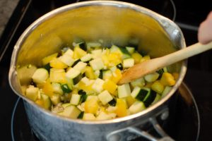 cooking chopped onion,zucchini, bell pepper, and garlic in a pot on the stove