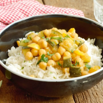spiced chickpea curry served on basmati rice in a black bowl