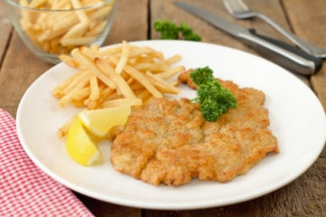 authentic german pork schnitzel served with fries, a wedge of lemon, and parsley on a white plate