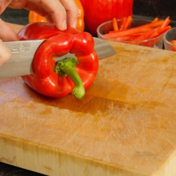 slicing into a red pepper on a wooden cutting board